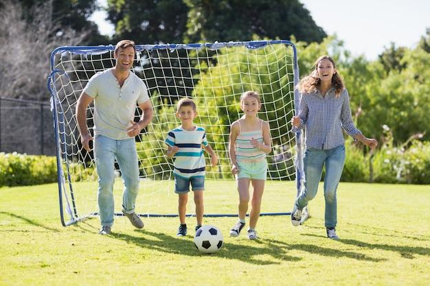 Família jogando futebol juntos no parque