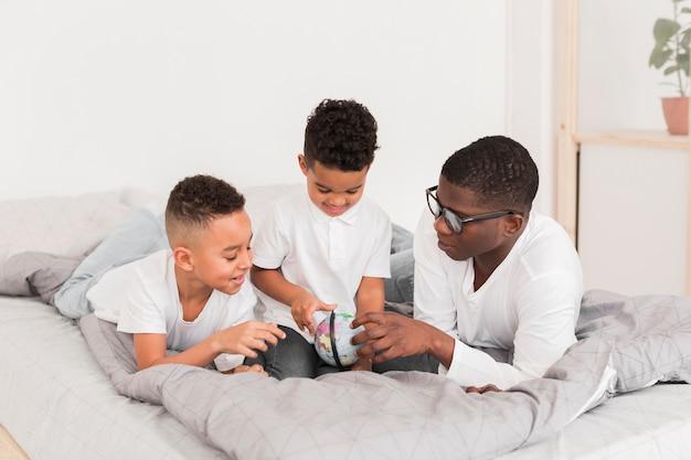 Família jogando junto com um pequeno globo na cama
