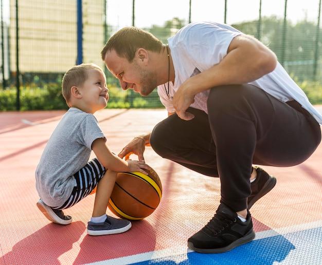 Família jogando no campo de basquete