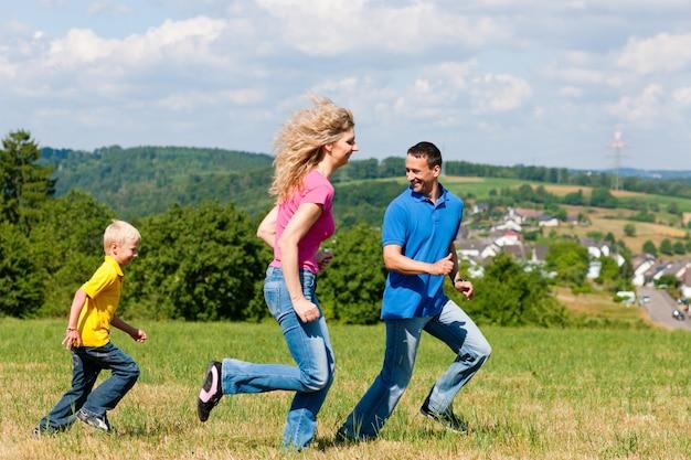 Família jogando tag no prado no verão