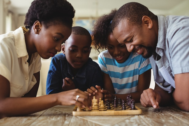 Família jogando xadrez juntos em casa, na sala de estar