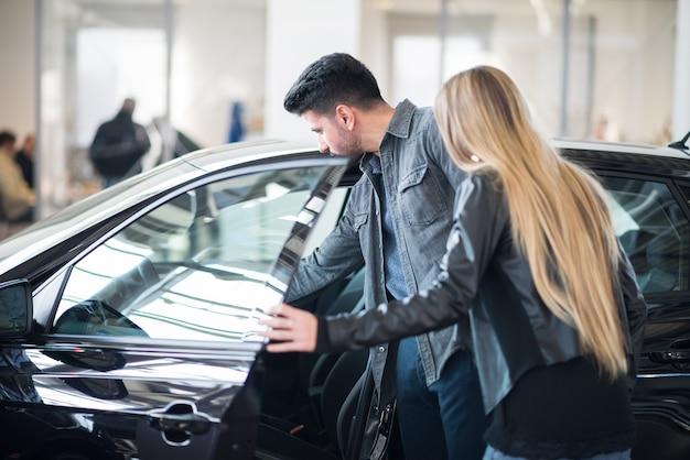 Família jovem à procura de sua compra de carro juntos