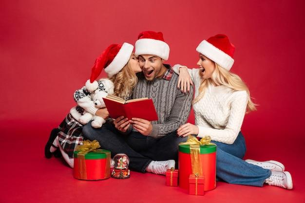 Família jovem alegre chocada usando chapéus de natal, lendo o livro.