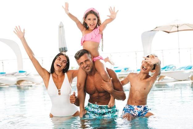 Família jovem animada se divertindo dentro de uma piscina