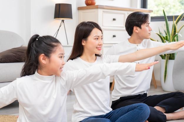 Família jovem asiática fazendo exercícios juntos em casa Foto Premium