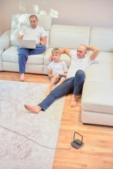 Família jovem assistindo televisão, dois caras e um menino sentado no sofá e no chão na sala de estar em casa