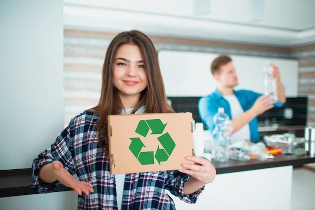 Família jovem classifica materiais na cozinha para reciclagem. os materiais recicláveis devem ser separados. a esposa está segurando uma caixa de papelão com um sinal verde de reciclagem. marido classifica lixo.