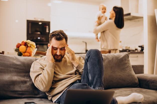 Família jovem com bebê pequeno, marido com dor de cabeça