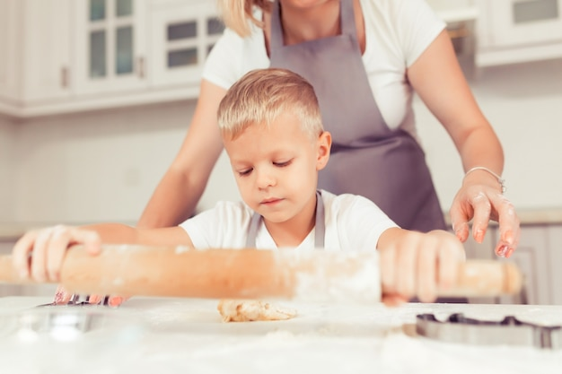 Família jovem com criança e filhos fazendo biscoitos de gengibre em casa.