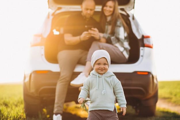 Família jovem com crianças que viajam de carro, parou no campo
