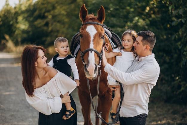 Família jovem com crianças se divertindo com o cavalo na floresta