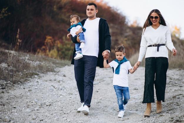 Família jovem com dois filhos juntos fora do parque