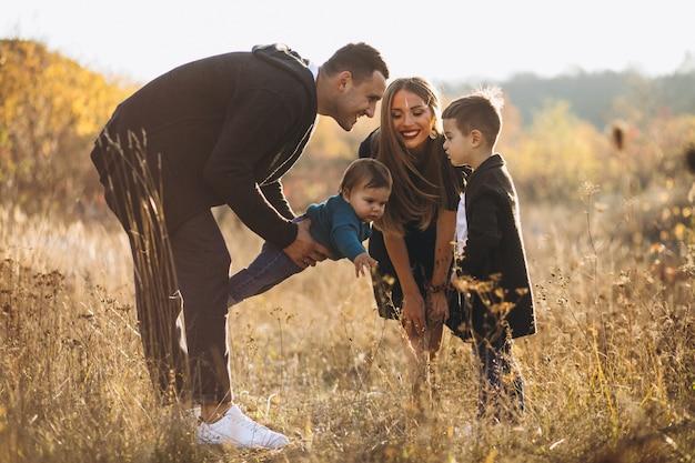 Família jovem com dois filhos juntos no parque