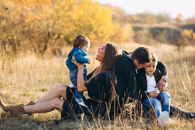 Família jovem com dois filhos juntos, sentado no parque