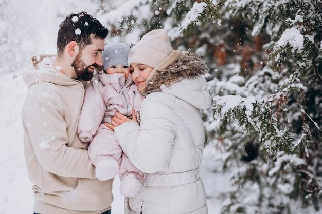Família jovem com filha em uma floresta de inverno cheia de neve