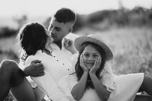 Família jovem com filha no prado
