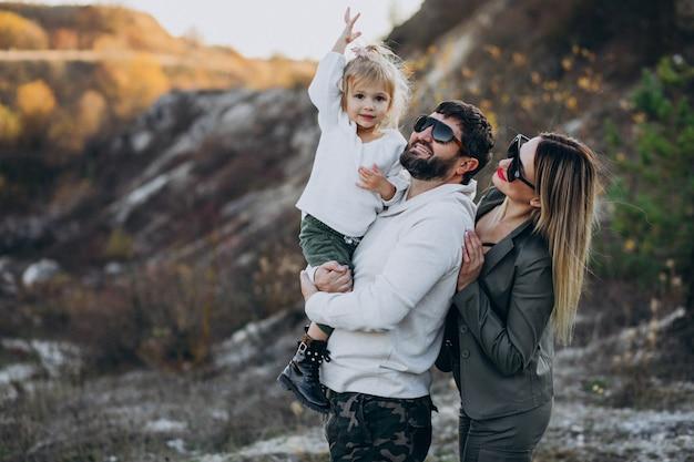 Família jovem com filha parada na floresta