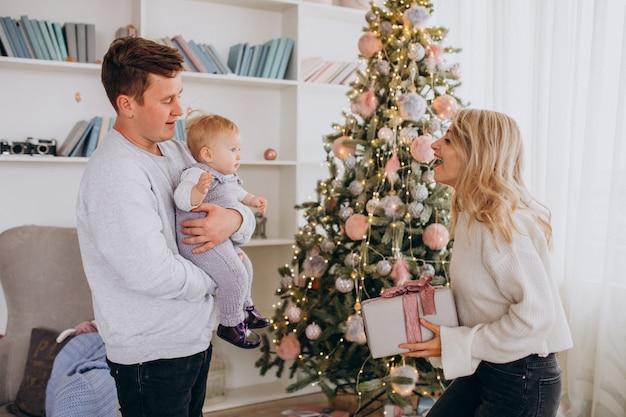 Família jovem com filha segurando presentes de natal
