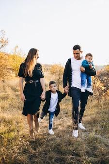 Família jovem com filho caminhando no parque