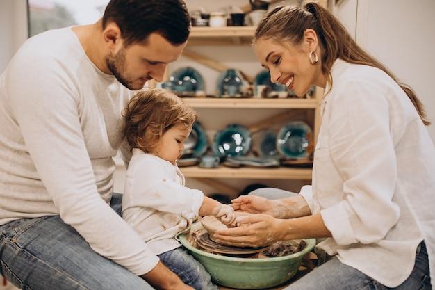 Família jovem com filho pequeno na aula de cerâmica