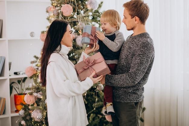 Família jovem com filho pequeno pela árvore de natal, segurando os presentes de natal