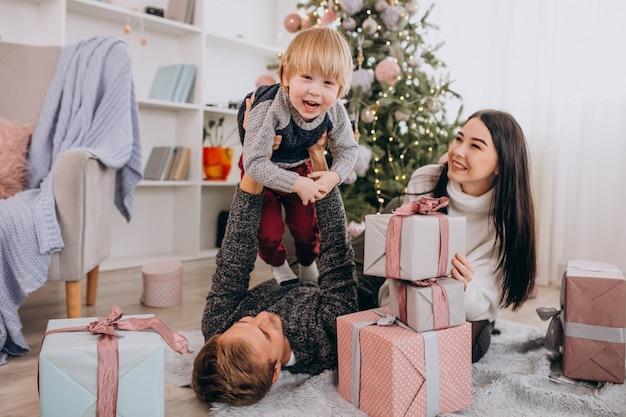 Família jovem com filho pequeno pela árvore de natal
