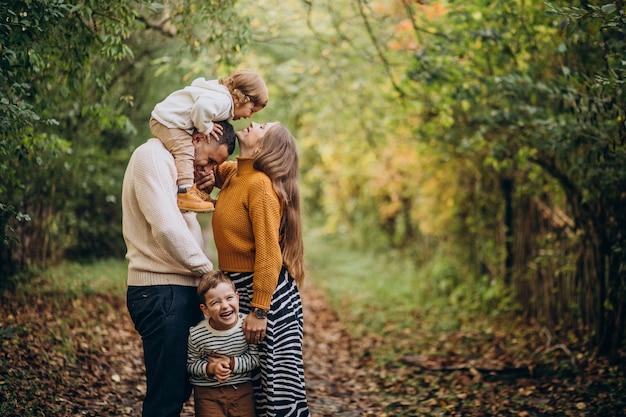 Família jovem com filhos no parque de outono