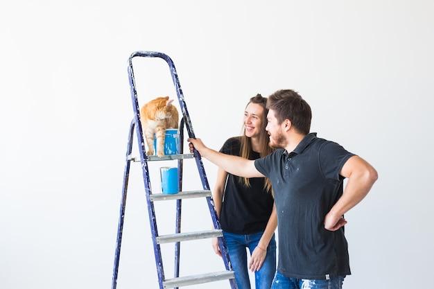 Família jovem com gato fazendo reparos e pintando paredes juntos e rindo.