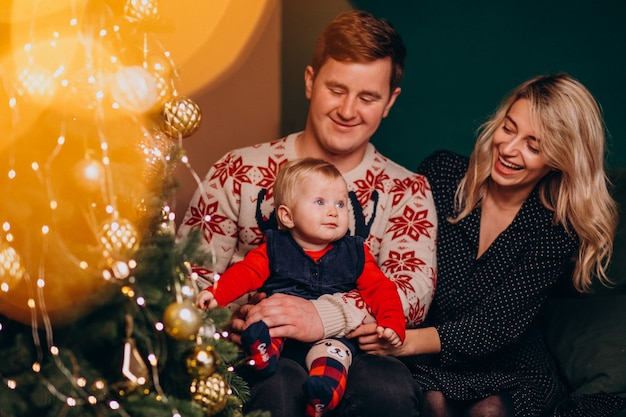 Família jovem com menina sentada perto de árvore de natal