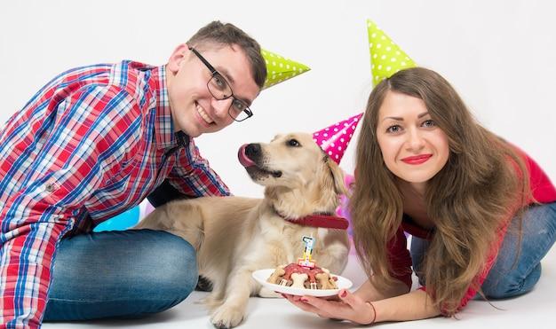 Família jovem com seu cão golden retriever comemorar aniversário de um ano.