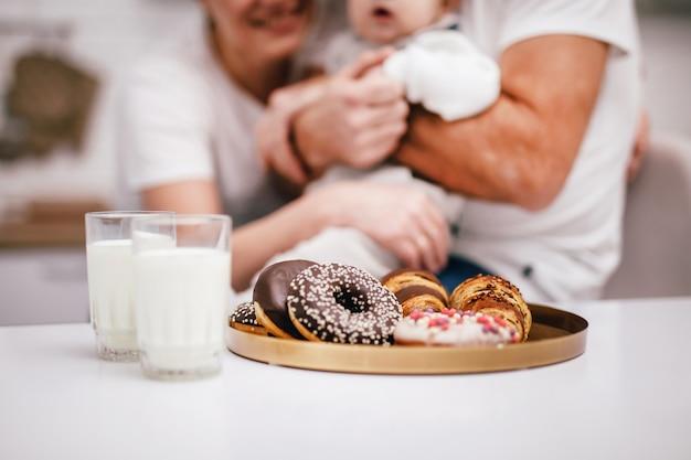 Família jovem com um bebê nos braços vai beber leite e tomar café da manhã