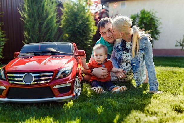 Família jovem com uma criança brincando na grama