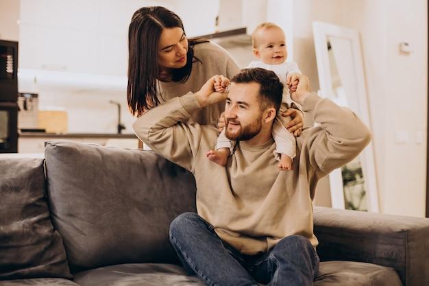 Família jovem com uma menina bebê em casa sentada no sofá