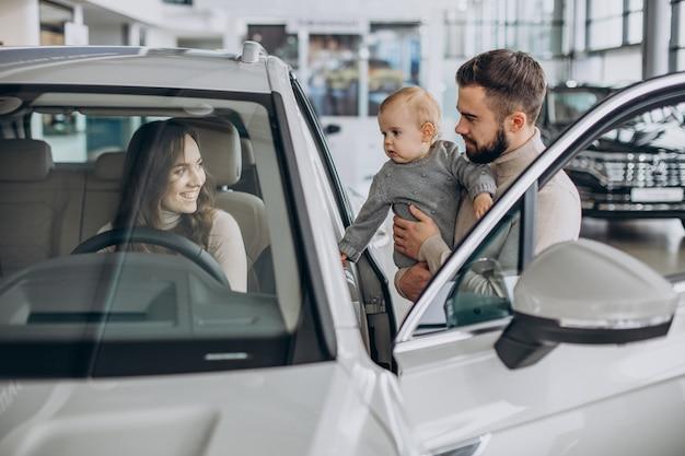Família jovem com uma menina escolhendo um carro