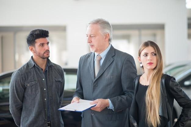 Família jovem conversando com o vendedor e escolhendo seu novo carro em um showroom