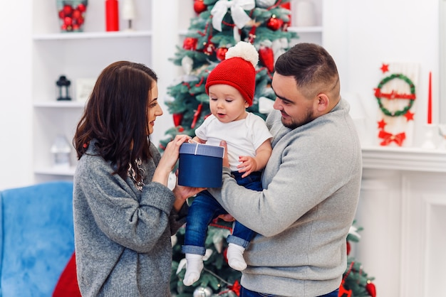 Família jovem dá a primeira caixa de presente de natal para seu filho recém-nascido. menino da criança recebe seu primeiro presente de natal.