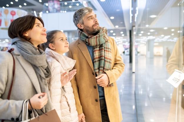 Família jovem de casacos parada perto da vitrine do shopping e discutindo sobre a nova coleção de roupas casuais enquanto fazia compras