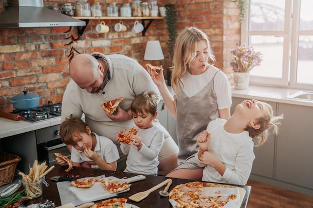 Família jovem de caucasianos degusta e come as pizzas que prepararam e aproveita as férias. garoto risonho gosta de pizza.