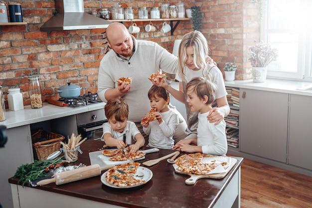 Família jovem de caucasianos degusta e come as pizzas que prepararam e aproveita as férias.