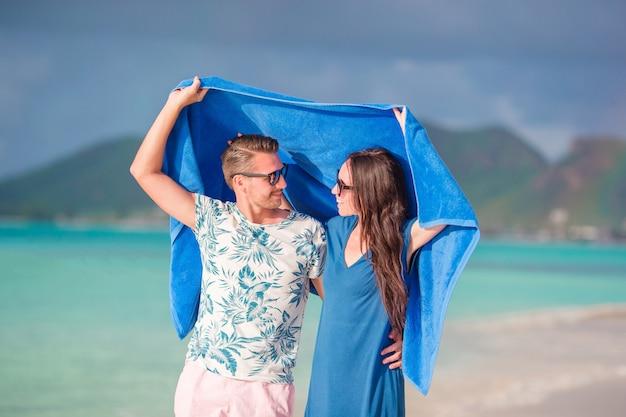 Família jovem de dois na praia tropical com toalha. praias e países tropicais remotos. conceito de viagens