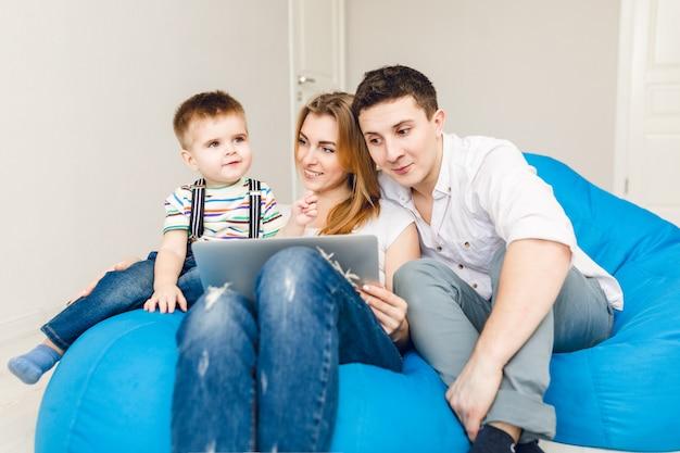 Família jovem de dois pais e um filho menino sentado em cadeiras de saco azuis.