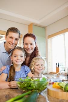 Família jovem de pé atrás do balcão da cozinha