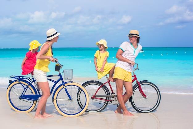 Família jovem, de, quatro, montando, bicycles, ligado, um, tropicais, praia areia