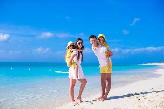 Família jovem de quatro pessoas em férias na praia