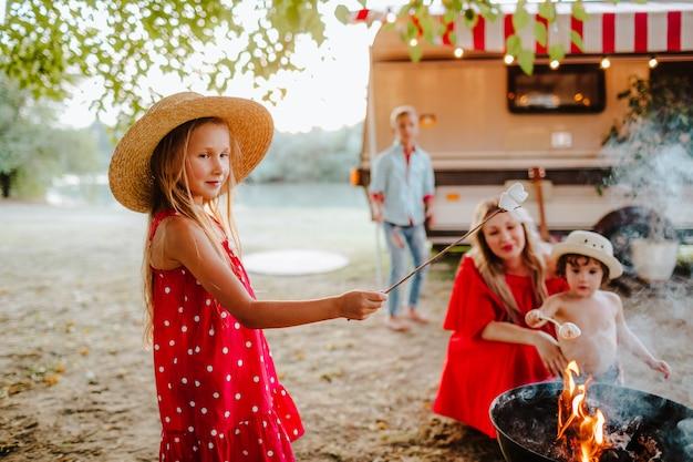 Família jovem de quatro pessoas fazendo piquenique