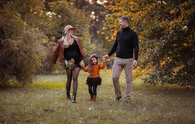 Família jovem de três com linda mãe grávida, filha e pai a passar tempo juntos