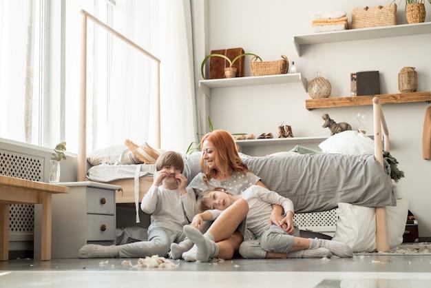 Família jovem descansando juntos na cama dos pais