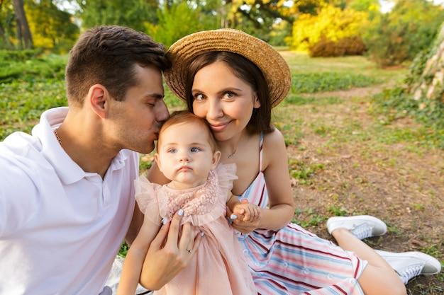 Família jovem e adorável com uma menina passando um tempo juntos