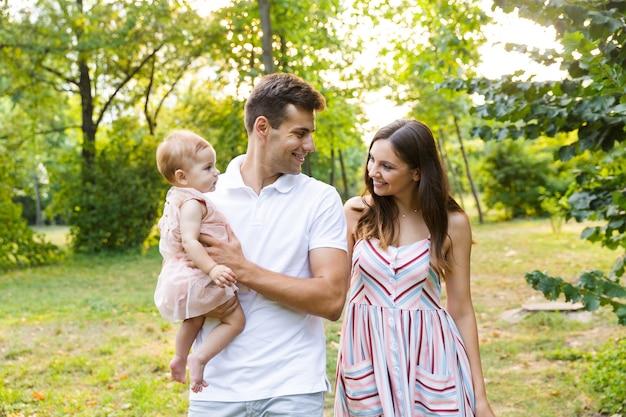 Família jovem e alegre com a garotinha passando o tempo