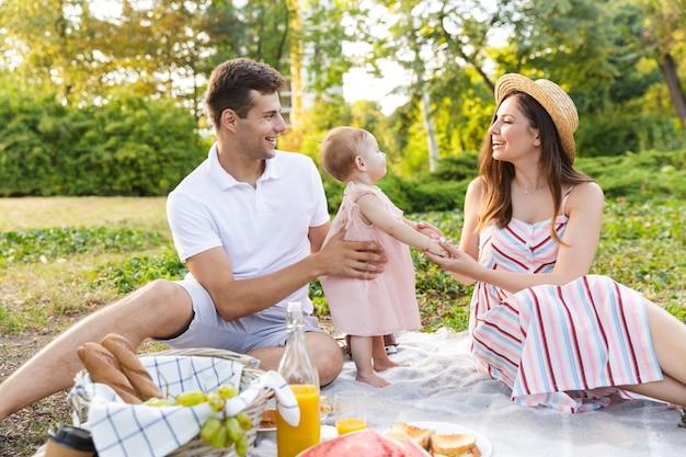 Família jovem e alegre com uma garotinha passando um tempo juntos